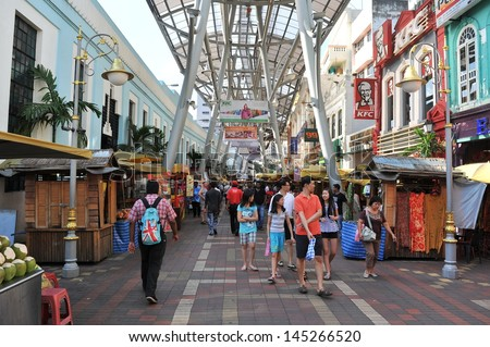 KUALA LUMPUR - MAY 13: Shoppers and traders walk along a bustling Chinatown street on Feb 13, 2013 in Kuala Lumpur. The city's ethnic Chinese began settling Chinatown Petaling Street area circa 1850s. - stock photo