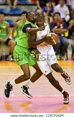 KUALA LUMPUR - OCT 28: Farmcochem's Chris Kuete (white) drives to the basket defended by Tiger's Decorey Jones in a Malaysia National Basketball League match on Oct 28, 2012 in Kuala Lumpur, Malaysia. - stock photo