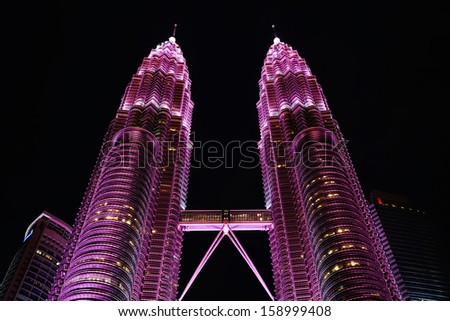 KUALA LUMPUR - OCT 19: Petronas Twin Towers illuminate in pink in conjunction of breast cancer campaign to raise awareness about breast health and early detection on October 19, 2013 in Kuala Lumpur - stock photo