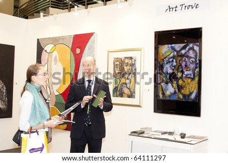 KUALA LUMPUR - OCTOBER 30: A visitor being brief by Art Trove representative during The Art Expo Malaysia held at Matrade Exhibition and Convention Centre October 30, 2010 in Kuala Lumpur, Malaysia.