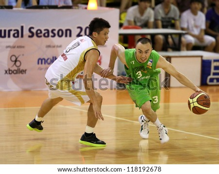 KUALA LUMPUR - OCTOBER 28: Crouching Tiger's Kevin van Hook #3 charges into Farmcochem's Ooi Ban Sin #7 in a Malaysia National Basketball League match on October 28, 2012 in Kuala Lumpur, Malaysia. - stock photo