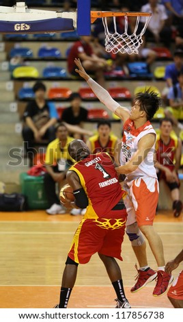 KUALA LUMPUR - OCTOBER 27: Farmcochem's Christopher Garnet #1 fakes a shot, defended by Dragons' John Ng in a Malaysia National Basketball League match on October 27, 2012 in Kuala Lumpur, Malaysia. - stock photo