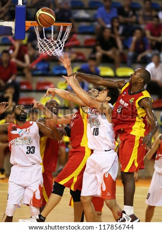 KUALA LUMPUR - OCTOBER 27: Farmcochem's player (red) and Dragons players (white) scramble for a loose ball in a Malaysia National Basketball League match on October 27, 2012 in Kuala Lumpur, Malaysia. - stock photo