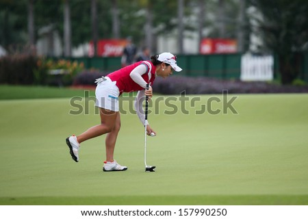 KUALA LUMPUR - OCTOBER 12: Hee Young Park picks up the ball after her putt at the 2nd hole green of the KLGCC course on Day 3 of the Sime Darby LPGA on October 12, 2013 in Kuala Lumpur, Malaysia. - stock photo