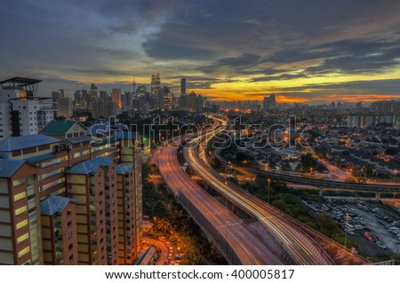 Kuala Lumpur skyline at dusk with lightrail and AKLEH highway as leading line