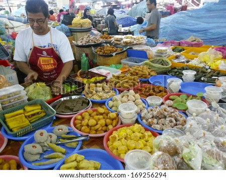 KUALA TERENGGANU, MALAYSIA-DEC. 22, 2013: Various local dishes on sale by local man in a local market in Kuala Terengganu, Trengganu, Malaysia on December 22, 2013.