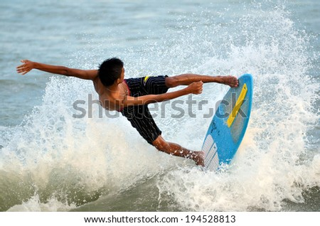 KUANTAN - DECEMBER 29: unidentified surfer in action catching waves in evening at Teluk Cempedak beach on December 29, 2012 in Kuantan, Pahang, Malaysia.