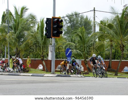 KUANTAN, MALAYSIA - MARCH 1: Group of riders in cornering action during race in stage 7 of the Le Tour de Langkawi from Bentong to Kuantan on March 1, 2012 in Kuantan, Malaysia. - stock photo