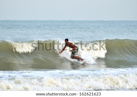 KUANTAN, MALAYSIA - 6 NOV 2013 - Surfer rides the back side of a wave during monsoon at Teluk Cempedak Beach, Pahang, Malaysia, on 6 Nov 2013. Teluk Cempedak beach are famous beach at Malaysia.