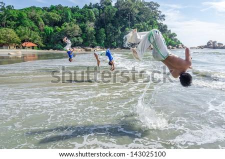 KUANTAN, PAHANG-JAN 5 : Backflip Jumping by capoeirasta at Teluk Cempedak beach, Kuantan, Pahang on Jan 5, 2013. Capoeira is an Afro-Brazilian art form that combines elements of martial arts and dance - stock photo
