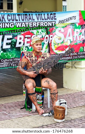 KUCHING, MALAYSIA - OCTOBER 13 :An unknown man from the Iban tribe playing sape, a traditional musical instrument. Photo taken October 13 2013 in Kuching, Malaysia.  - stock photo