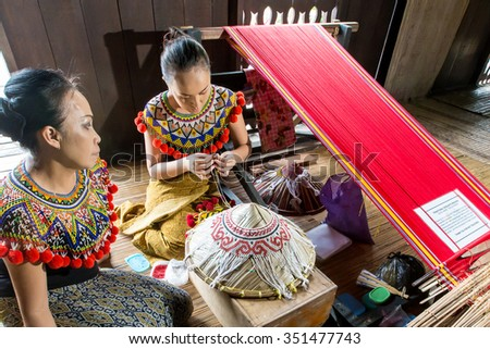 KUCHING, SARAWAK, MALAYSIA - Decemver 14, 2015: The etnik Iban lady of Borneo crafting an exotic hand made native handicraft at Sarawak Culture Village.