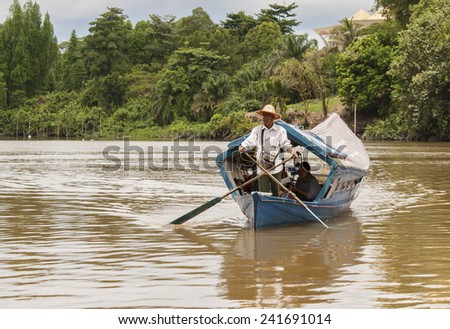 KUCHING, SARAWAK - SEPTEMBER 24: Man rowing a traditional river boat transporting people across Sarawak River on September 24, 2010 in Kuching, Sarawak. This river boat is Kuching city famous icon