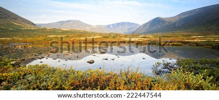 Kukisvumchorr plateau mountain ridge reflected in still freshwater Polygonal lake with dwarf birch and willows on its edges - stock photo