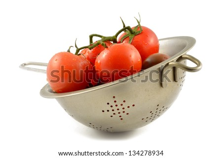 Kumato tomato and red tomato in a colander - stock photo