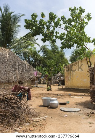 KUMBAKONAM, INDIA - OCTOBER 11, 2013: A group of humble houses, some with straw roofs and mud walls stand at a dusty, sandy walkway. Kitchen utensils are strewn on the ground. Firewood is piled up. - stock photo