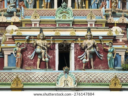 KUMBAKONAM, INDIA - OCTOBER 12, 2013: Mahalingeswarar Temple. Two Dwarapalakas, door keepers of Lord Shiva. Detail of the tall Gopuram above the main entrance to this very large Shiva temple.
