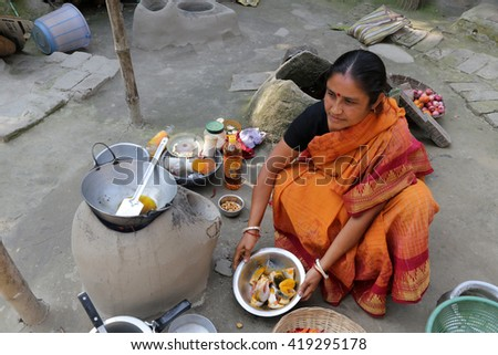 KUMROKHALI, INDIA - FEBRUARY 13: Traditional way of making food on open fire in old kitchen in a village, Kumrokhali, West Bengal, India February 13, 2014. - stock photo