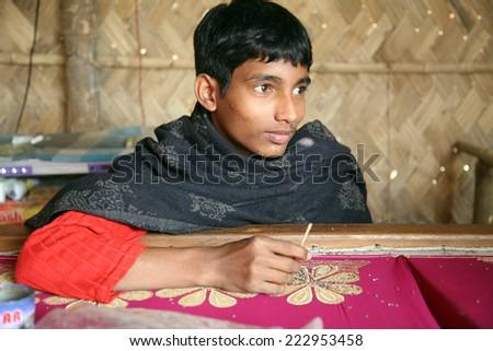 KUMROKHALI, INDIA - JAN 16: Anandalok Naskar working on the decoration of textiles in Kumrokhali, India on Jan 16, 2009. - stock photo