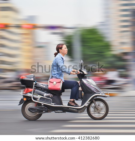 KUNMING, CHINA-JULY 5, 2014. Young woman on electric bike. Many electric bikes in China are the scooter style e-bike that may or may not have pedals. The Chinese e-bike market is the largest in the world. - stock photo