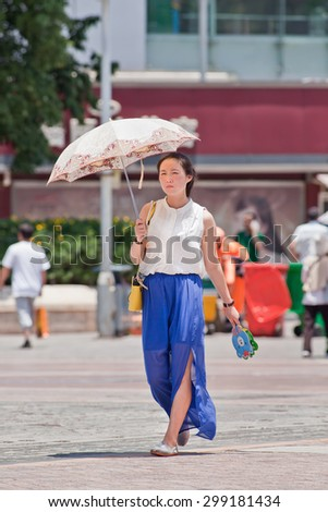 KUNMING-JULY 10, 2014. Pretty Chinese girl with umbrella as sun blocker. Since ancient times a pale skin is an absolute Chinese beauty ideal. A tanned skin is often associated with low class workers. - stock photo