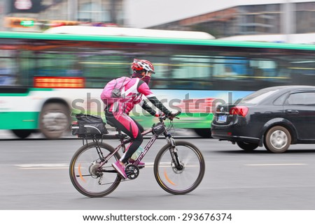 KUNMING-JULY 5, 2014. Sporty woman on Merida bike. Merida is a Taiwanese manufacturer of bicycles and accessories. The brand designs and manufactures city bikes, mountain bikes and racing bikes.  - stock photo