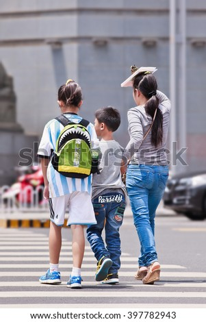 KUNMING-JULY 5, 2014. Woman with children on zebra crossing. Xinhua reported on 29 Oct. 2015 the new policy allowing Chinese couples to have two children in order to help address China's aging issue.