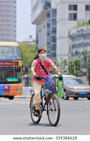 KUNMING-JULY 5, 2014. Woman with mouth cap on bicycle. An increasing number of Chinese citizens wear breath protection, only eight out of China's 74 biggest cities passed 2014 air quality standards. - stock photo