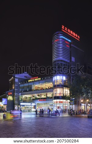 KUNMING-JULY 2, 2014. Zhengyi Fashion Shopping mall at night. Kunming is a shoppers paradise, its streets and plazas are filled with malls, department stores, chain-store supermarkets, and boutiques. - stock photo