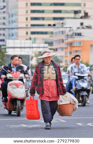 KUNMING-JUNE 30, 2014. Elder woman carries bag and bucket with stuff on the road. China's elderly population (60 or older) is about 128 million, one in every ten people, the largest in the world. - stock photo