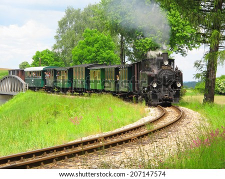 KUNZAK-LOMY, CZECH REPUBLIC - MAY 31: Steam train passes over a bridge on May 31, 2014. Historic locomotive from year 1907 on narrow gauge railway track between cities Jindrichuv Hradec - Nova Bystrice. - stock photo