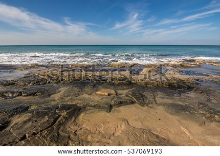 Kurkar sandstones along the coast of Nahariya with feather clouds in the background