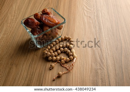 Kurma or dried dates fruit and rosary on wooden background. Dates are popular as food supplement during Ramadan among Muslims during iftar. - stock photo