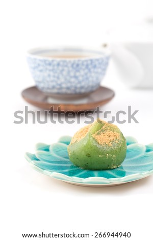 Kusa mochi (kusamochi or yomogi mochi) is a traditional Japanese confectionery (wagashi) made from mochi and leaves of Japanese mugwort (yomogi). Filled with red bean paste (anko). Served with kinako. - stock photo