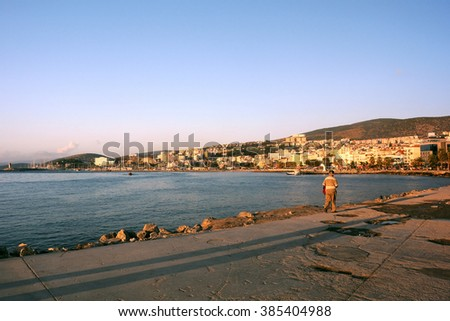KUSADASI, TURKEY - OCTOBER 4, 2009: View of the port area and the town in the background at sunset - stock photo