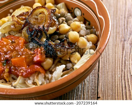 Kushari - is an Egyptian dish of rice, macaroni and lentils mixed together, topped with a tomato-vinegar sauce; some add short pieces of spaghetti garnished with chickpeas and crispy fried onions - stock photo