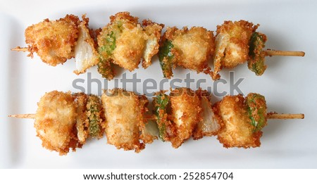 Kushi sticks or fried chicken skewers on a plate. - stock photo