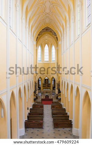 KUTNA HORA, CZECH REPUBLIC - AUGUST 22, 2016: Interiors of empty Church Chram Nanebevzeti Panny Marie, seats and altar