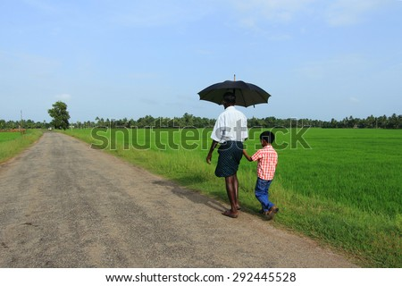 KUTTANAD, INDIA - JUL 03 : An unidentified farmer walks with a boy long the paddy fields on July 03, 2012 in Kuttanad,India. Paddy is the major crop in the region that's situated below the sea level. - stock photo