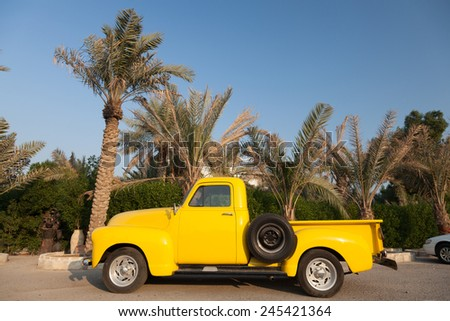 KUWAIT - DECEMBER 11: Classic yellow Chevy pickup truck parked under the palm trees in Kuwait City. December 11, 2014 in Kuwait, Middle East - stock photo