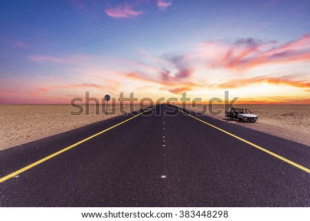 Kuwait wafra road through the desert and clouds during the sunset - stock photo