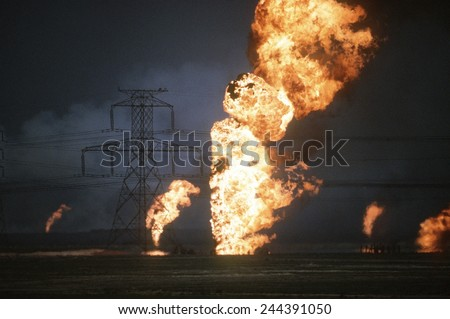 Kuwaiti oil wells set on fire by retreating Iraqi forces during Operation Desert Storm darken the sky with smoke. Mar. 25 1991 - stock photo