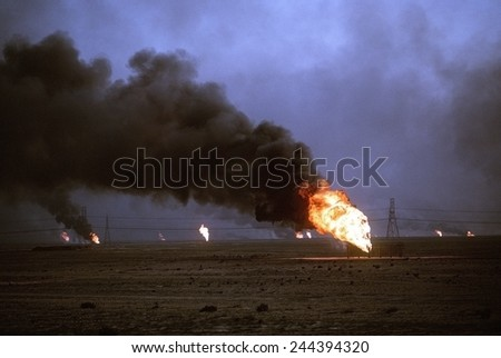 Kuwaiti oil wells set on fire by retreating Iraqi forces during Operation Desert Storm darken the sky with smoke. Mar. 1 1991 - stock photo