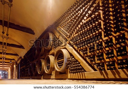 KVARELI, GEORGIA - OCT 3: Rows of oak barrels and bottles inside huge cellar Khareba Winery with cold underground tunnel on October 3, 2016. The tunnel was opened in 1962 for the World Wine Congress