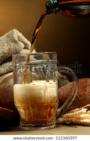 kvass poured into a mug  and rye breads with ears, on wooden table on brown background