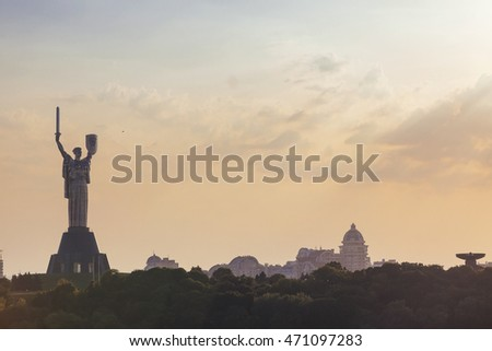 Kyiv - August 2016: Motherland monument with sword and shield with former USSR state emblem opened in 1981 at sunset and skyline, August 06, 2016, Kyiv, Ukraine