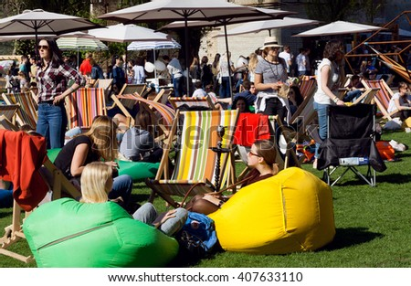 KYIV, UKRAINE - APR 17: Crowded party with relaxing people under umbrellas at green lounge area of outdoor Street Food Festival on April 17, 2016. Kiev is the 8th most populous city in Europe. - stock photo