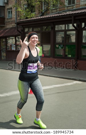 KYIV, UKRAINE - APRIL 28: Middle aged woman smiling and saluting during 5-th Wizz Air Kyiv City Marathon, a competition run of 42 km held in the old city center on April 28, 2013 in Kyiv, Ukraine.  - stock photo