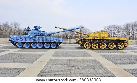 KYIV, UKRAINE - CIRCA APRIL, 2013: Two painted  old USSR tanks with crossed  trunks in Ukrainian flag colors as pacific symbol. The state museum of Second World War.