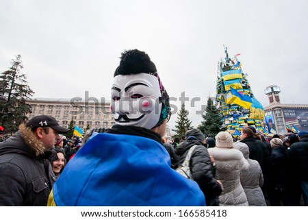 KYIV, UKRAINE - DEC 8: Protester with Guy Fawkes mask in the crowd of people on the occupying street during two weeks anti-government protest on December 8, 2013, in Kiev, Ukraine. - stock photo